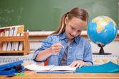 Smiling schoolgirl doing classwork — Stock Photo