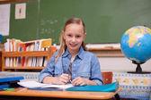 Cute schoolgirl doing classwork — Stock Photo