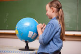 Schoolgirl looking at a globe — Stock Photo