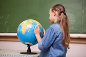 Focused schoolgirl looking at a globe — Stock Photo
