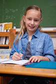 Portrait of a smiling schoolgirl writing — Fotografia Stock