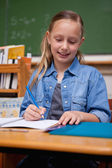 Portrait of a happy schoolgirl writing — Fotografia Stock