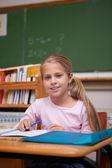 Portrait of a cute schoolgirl writing — Stock Photo