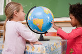 Smiling schoolgirls looking at a globe — Stock Photo