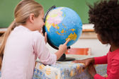 Little schoolgirls looking at a globe — Stock Photo