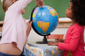 Cute little schoolgirls looking at a globe — Stock Photo