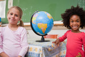 Schoolgirls posing with a globe — Stockfoto