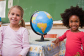 Cute schoolgirls posing with a globe — Stock Photo