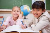Smiling schoolgirls doing classwork — Stock Photo