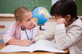 Cute schoolgirls doing classwork — Stock Photo