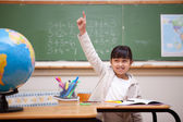 Smiling schoolgirl raising her hand to answer a question — Stock Photo