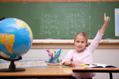 Cute schoolgirl raising her hand to answer a question — Stock Photo