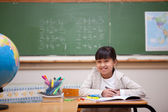 Smiling schoolgirl drawing on a coloring book — Stock Photo