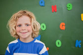 Schoolboy posing in front of a blackboard — Stock Photo