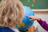 Finger of a little girl showing a country to a classmate — Stock Photo