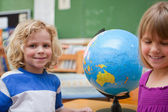Young pupils posing in front of a globe — Stock Photo