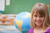 Schoolgirl posing in front of a globe — Stock Photo