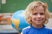 Schoolboy posing in front of a globe — Stock Photo