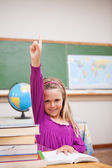 Retrato de joven colegiala levantando su mano — Foto de Stock