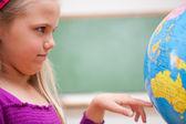 Close-up de uma menina a olhar para um globo de — Foto Stock