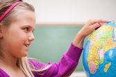 Vicino di una studentessa carina guardando un mappamondo — Foto Stock