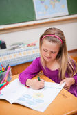 Portrait of a cute schoolgirl drawing — Stock Photo