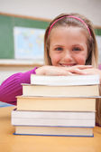Retrato de una niña sonriente posando con una pila de libros — Foto de Stock