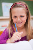 Portrait of a little schoolgirl writing on a book — Stock Photo