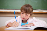 Serious girl writing — Stock Photo