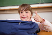 Cute schoolgirl posing with a bag and the thumb up — Stock Photo