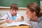 Cute schoolgirl writing a while her teacher is talking — Stock Photo