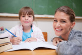 Schoolgirl writing with her teacher — Stock Photo
