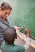 Portrait of a beautiful teacher and a pupil making an addition — Stock Photo