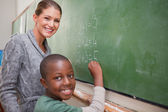 Smiling teacher and a pupil making an addition — Stock Photo