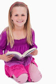 Portrait of a smiling girl reading a book — Stock Photo