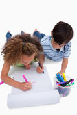 Portrait of children drawing while lying on the floor — Stock Photo
