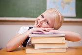 Menina sorridente, inclinando-se sobre os livros — Foto Stock