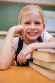 Retrato de una niña sonriente apoyándose en libros — Foto de Stock
