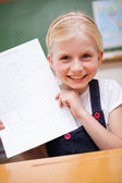 Portrait of a happy girl showing her school report — Stock Photo