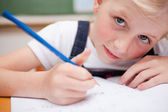 Close up of a serious schoolgirl writing something — Stock Photo