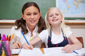 Smiling pupils working together on an assignment — Stock Photo