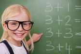 Smart schoolgirl pointing at something — Stock Photo