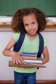 Portrait of a schoolgirl holding books — Stock Photo