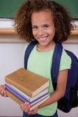 Retrato de una colegiala sosteniendo sus libros — Foto de Stock