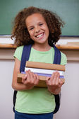 Portrait of a smiling schoolgirl holding her books — Stock Photo