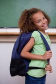Portret uczennica pokazano jej plecak — Zdjęcie stockowe