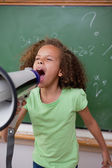 Portrait of a cute schoolgirl screaming through a megaphone — Stock Photo