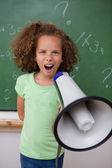 Portrait of a young schoolgirl screaming through a megaphone — Stock fotografie