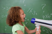 Side view of a schoolgirl screaming through a megaphone — Stock Photo