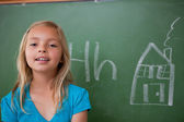 Blonde schoolgirl posing in front of a blackboard — Stock Photo